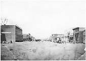 Grand Ave., Del Norte, looking west at the business district.  There seems to be lots of activity; transport is only by animal power.<br /> Del Norte, CO  1874