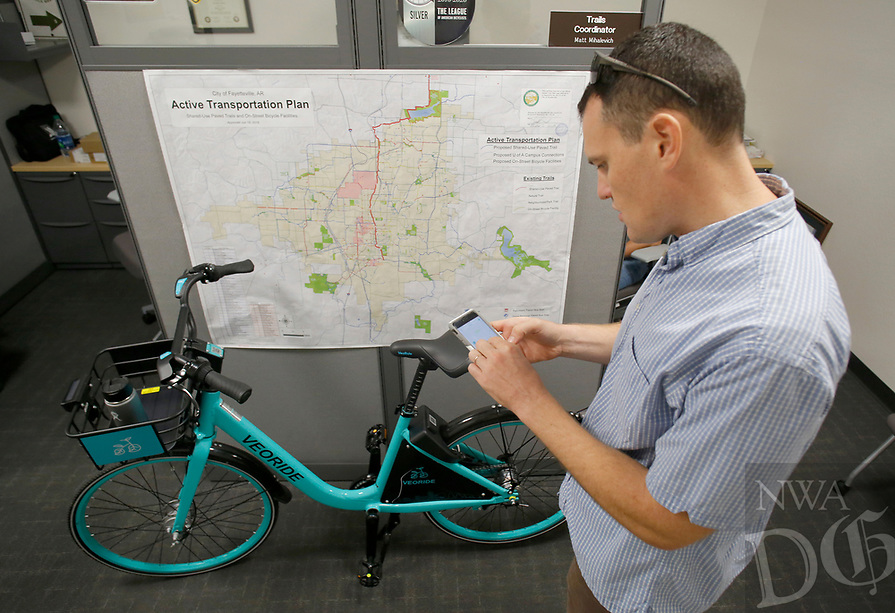 NWA Democrat-Gazette/DAVID GOTTSCHALK Dane Eifling, Bicycle and Pedestrian Program Coordinator with the University of Arkansas and city of Fayetteville, demonstrates Friday, August 3, 2018, the VeoRide app to unlock one of the demonstration bikes for the new bike-share program in the city. The city of Fayetteville, University of Arkansas, Fayetteville and Experience Fayetteville teamed up to bring the program for the bikes that will be red and white with signage.