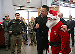 From left, Sgt. Daniel Gonzales, Gov. Brian Sandoval and Santa welcome volunteers to the 14th annual Holiday with a Hero shopping day in Carson City, Nev., on Monday, Dec. 20, 2017.<br />