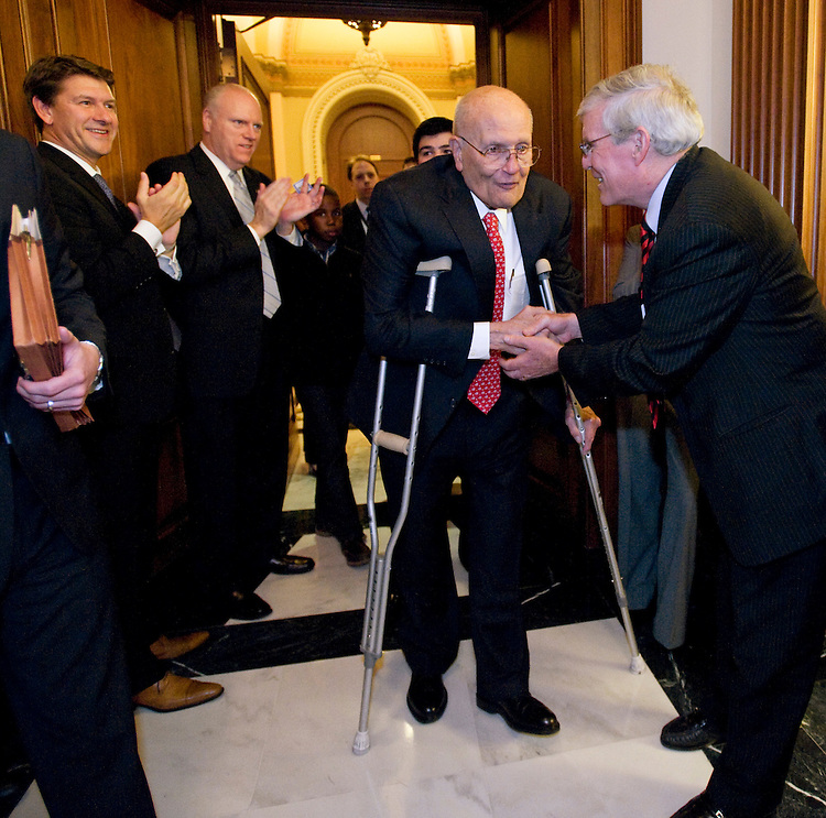 WASHINGTON, DC - Nov. 07: Rep. John D. Dingell, D-Mich., with crutches, shakes hands with Ron Pollack, executive director of FamiliesUSA, as he arrives for a news conference after the House passed most ambitious overhaul of the U.S. health care system in 40 years, allowing President Obama to win a preliminary round in what could still be a long battle for his top domestic priority. Like his father before him, Dingell has championed universal health care throughout his 54-year House career. Dingell also presided as the House debated the rule governing consideration of the bill, just as he wielded the gavel 40 years ago when the House considered the Medicare bill. The 220-215 vote for the trillion-dollar effort to extend health coverage to millions of Americans who currently lack it capped a long debate during which a soporific tone belied the tension within the majority Democratic caucus. Standing to Dingell's right is Rep. Joseph Crowley, D-N.Y.  (Photo by Scott J. Ferrell/Congressional Quarterly)