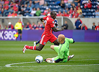 Chicago forward Dominic Oduro (8) knocks the ball away from oncoming New England goalkeeper Matt Reis.  Oduro would recover the ball and score on the play.  The Chicago Fire defeated the New England Revolution 3-2 at Toyota Park in Bridgeview, IL on Sept. 25, 2011.