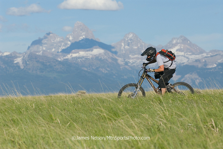 A mountain biker rides a ridgeline in the Big Hole Range of eastern Idaho, with the Teton Range of western Wyoming on the horizon.
