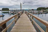Man walks the harbor dock in the coastal town of Yakutat, Alaska.