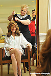 Bride with hair dresser in bridal suite at the Essex House in NYC, prior to her ceremony...