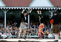 Scottish couple in tartan kilts dancing the sword dance at the Braemar Royal Highland Gathering, the Braemar Games in Scotland