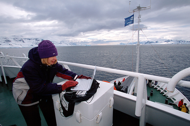 Woman tourist downloading a digital camera to a laptop computer on the deck of a tourist ship in Antarctica