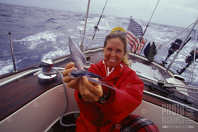 Woman in red jacket holding flying fish, aboard  sailing yacht 'Heron', Pacific equatorial ocean crossing from French Polynesia to Hawaii