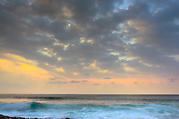 Distant surfers (on the left) wait for the right wave at sunset, Magic Sands beach, Kailua-Kona, Big Island.