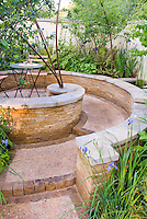 Small circular walled patio with blue iris and Digitalis foxglove, table and chairs, sense of enclosure and privacy, backyard deck landscaping