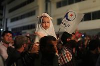23 ottobre 2011 Tunisi, elezioni libere per l'Assemblea Costituente, le prime della Primavera araba: sostenitori del partito Enhada festeggiano in piazza la vittoria del proprio partito la sera in cui vengono annunciati i risultati. Primo piano di una bambina con il velo in braccio al padre. In mano ha la bandiera di Enhada.<br /> premieres elections libres en Tunisie octobre <br /> tunisian elections Festeggiamenti vittoria Ennhada