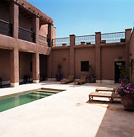 A long narrow pool in an inner courtyard is furnished with wicker sun-loungers