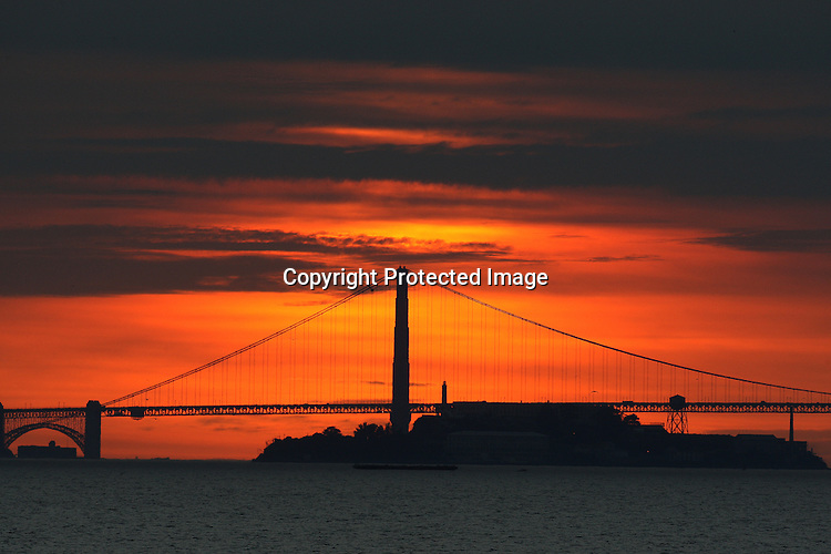 The sun set behind the Golden Gate Bridge and Alcatraz Island is huge from the Berkeley pier, California.