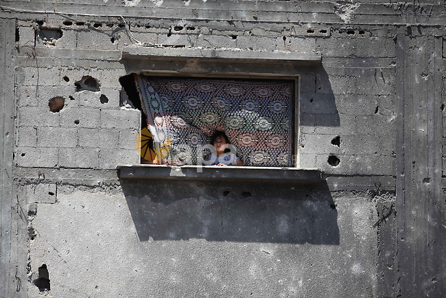 A Palestinian girl looks through a window house that witnesses said were destroyed in an Israeli offensive, after a ceasefire was declared in the Shejaia neighbourhood, east of Gaza City. September 6, 2014. Calm returned to the coastal enclave in a August 26 ceasefire, and Gazans were gradually starting to rebuild their lives after a bloody and destructive 50-day war, the deadliest for years. Photo by Ashraf Amra