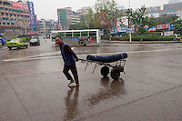 Daytime landscape view of a man pulling a hand cart on Hui Long Jie in Lóngmǎtán Qū of the Lúzhōu Prefecture City in Sichuan Province.  © LAN