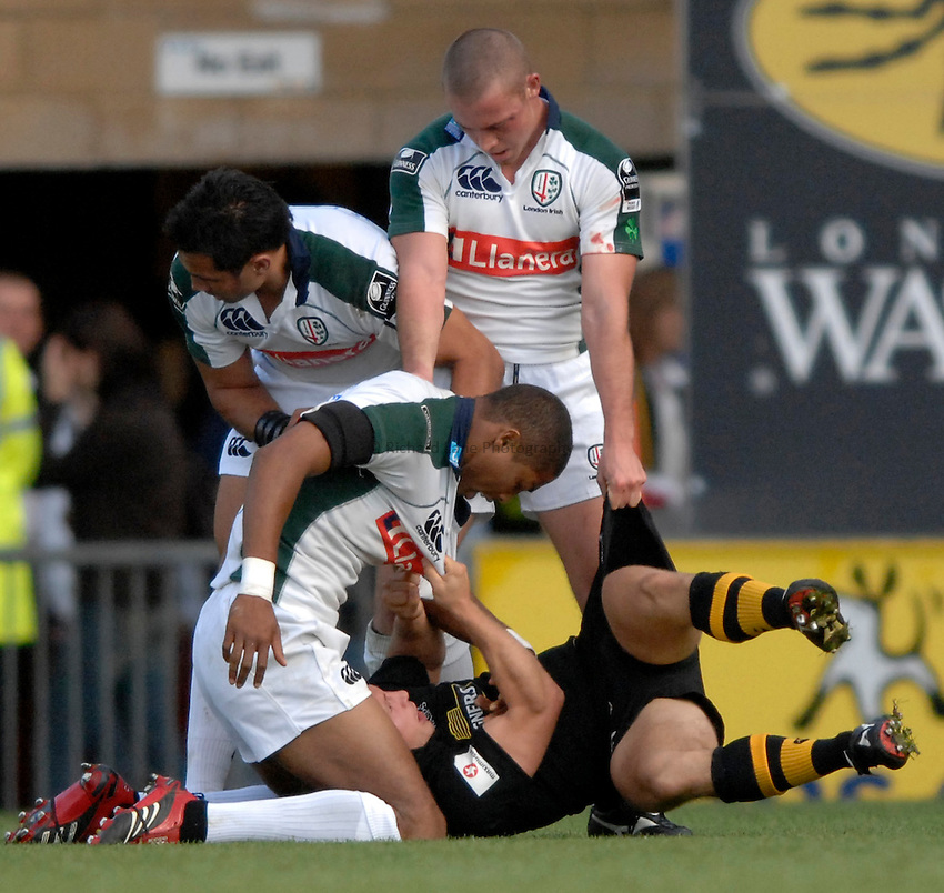 Photo: Richard Lane..London Wasps v London Irish. EDF Anglo-Welsh Cup. 08/10/2006. .Wasps' Simon Amor is held down after he is tackled high by Irish's Delon Armitage.