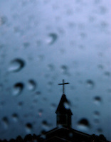 Rick Wilson Photo--7/16/04--Rain drops collect on a window surface as a church steeple looms in the background during a Summer afternoon rain shower in Jacksonville, Florida.