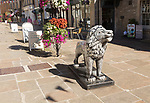 Lion sculpture in historic street and buildings in town centre of Corsham, Wiltshire, England, UK