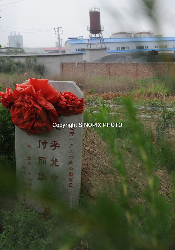 "Grave-stones outside a factory at Xiditou.  A sleent form of protest in the area by those who suffer from cancer is caused by factories in the area is to get buried out-side the factories.  Xiditou is known as one of China's worse ""cancer villages"" where a reported ten percent have died from cancer."