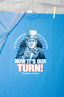 "A street vendor sells Trump-themed memorabilia as people gather near the National Mall to watch the inauguration of President Donald Trump on Jan. 20, 2017, in Washington, D.C. A t-shirt in the picture shows Trump dressed as Uncle Sam with the phrase, ""Now it's our turn!"""