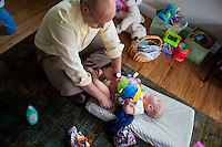 Fred Bermont dresses son Dylan Bermont (age 9 months) while daughter Elyse Bermont (left, age 2.5) plays in a tent in their home in Lexington, Massachusetts, USA, before he goes to work and drops the kids off at day-care on June 9, 2014. Bermont is the father of two children and shares parenting duties with his wife, Jen Bermont. Fred usually takes care of the morning routine, including feeding, dressing, and dropping the kids off at day-care, and Jen picks them up and watches over them in the afternoon. Fred is a Senior Clinical Standards Specialist at Shire, a pharmaceutical company with headquarters in Lexington.