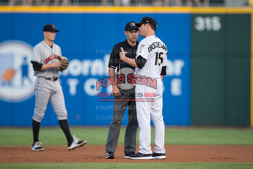 Charlotte Knights manager Mark Grudzielanek (15) discusses a call with second base umpire Dan Merzel during the game against the Indianapolis Indians at BB&T BallPark on June 16, 2017 in Charlotte, North Carolina.  The Knights defeated the Indians 12-4.  (Brian Westerholt/Four Seam Images)