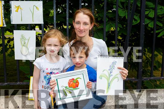 Harriet McKenna from Ballymac, displaying her work at the Art Exhibition in Denny Street on Saturday morning.<br /> L-r Harriet, Sophie and Oisin McKenna.