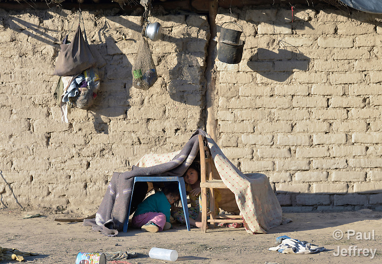 Six-year old Sara Torrijo, a Wichi indigenous girl in Santa Victoria Este, Argentina, sits in a play house she made of chairs and blankets in front of her family's home in the San Luis neighborhood. The Wichi in this area have struggled for decades to recover land that has been systematically stolen from them by cattleraisers and large agricultural plantations.