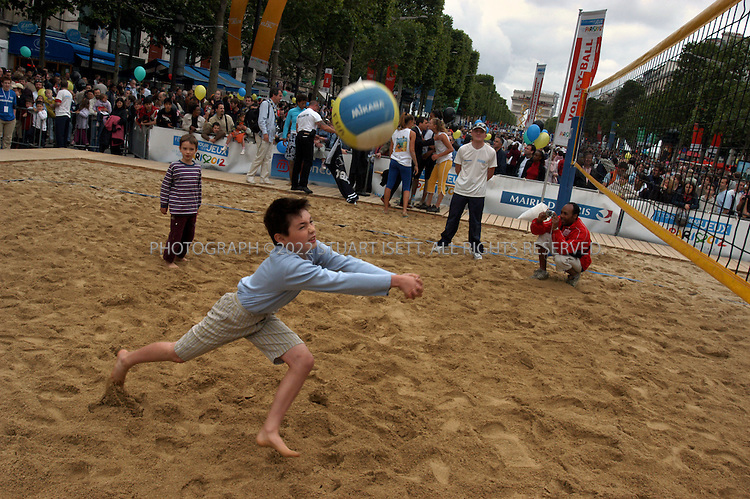 6/5/2005--Paris, France..A young French boy joins in a game of beach volley ball with other children during the 'Fetons l'Amour des Jeux' ('Celebrate the love of the Games') event today on the Champs-Elysées which invited members of the public to participate in numerous Olympic sports on Paris's most famous street. Paris has put in an ambitious bid for the 2012 Olympics, competing with New York, Moscow, London and Madrid and considered a lead candidate city...The Champs-Elysées was transformed into a symbolic ?Champs  Olympiques? with 28 Olympic disciplines grouped around a gigantic 700 m athletics track running from the Arc de Triomphe to Avenue  George V. Boxing rings, tennis courts, a rowing  pool and a hockey pitch were also set up..Photograph By Stuart Isett.All photographs ©2005 Stuart Isett.All rights reserved.