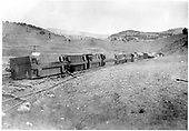 Ten or more box cars lying on sides and off track.  Twisted rail in foreground.  Sign reads Los Pinos.  Roofs of cars in scene.<br /> D&amp;RGW  Los Pinos, CO