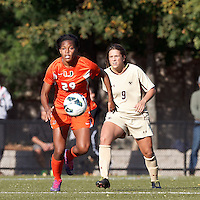 University of Miami forward Blake Stockton (29) brings the ball forward as Boston College forward Stephanie McCaffrey (9) closes..After two overtime periods, Boston College (gold) tied University of Miami (orange), 0-0, at Newton Campus Field, October 21, 2012.