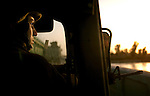 Lance Corporal Luis Colon from the 1st Marine Division keeps watch while traveling in a convoy  to a base in Ramadi on Sunday, May 18, 2004.  (photo by Khampha Bouaphanh)