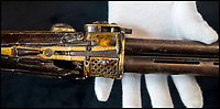 BNPS.co.uk (01202) 558833<br /> Pic: PhilYeomans/BNPS<br /> <br /> History in his hands - The trigger, lock and stock have been badly damaged by a musket ball - possibly leading to Tipu Sultan's demise.<br /> <br /> Stunning artefacts from Indian hero Tipu Sultan's fateful last stand have been rediscovered by the family of an East India Company Major who took part in the famous battle that ended his reign.<br /> <br /> And now Major Thomas Hart's lucky descendents are likely to become overnight millionaires after retrieving the historic items from their dusty attic.<br /> <br /> The fascinating treasures were taken from Tipu's captured fortress of Seringapatam in the wake of his defeat by British forces led by a young Duke of Wellington in 1799.<br /> <br /> The cache of ornate gold arms and personal effects even include's the battle damaged musket the Sultan used in his fatal last stand against the expanding British Empire in India.<br /> <br /> Tipu was last seen on the battlements of the fortress firing his hunting musket at the advancing British and after the fierce encounter his body was found bearing many wounds, including a musket ball shot above his right eye.<br /> <br /> The rediscovered musket, complete with battle damaged bayonet, has the distinctive tiger stripe pattern unique to the self styled Tiger of Mysore own weapons - and tellingly there is also shot damage to the lock and stock that may have been caused by the musket ball that finished him off.<br /> <br /> Also included in the sale are four ornate gold-encrusted sword's bearing the mark of Haider Ali Khan, Tipu's father and the previous ruler of independent Mysore, along with a solid gold &lsquo;betel casket&rsquo; complete with three 220 year old nuts still inside.<br /> <br /> The war booty was brought back to Britain by Major Thomas Hart of the British East India Company following the fourth and final Anglo-Mysore war.<br /> <br /> They have been passed down through the family ever since and now belong to a couple who have kept them wrapped in newspaper in the dusty attic of their semi-detached home for years.