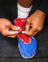 Jordan Burroughs of the United States (cq) tapes up the laces on his shoes in the locker room before the final round of the Pan American Championships at Dr. Pepper Arena in Frisco, Texas, Saturday, Saturday 27, 2015. Burroughs eventually won gold at the event.<br /> <br /> Photo by Matt Nager