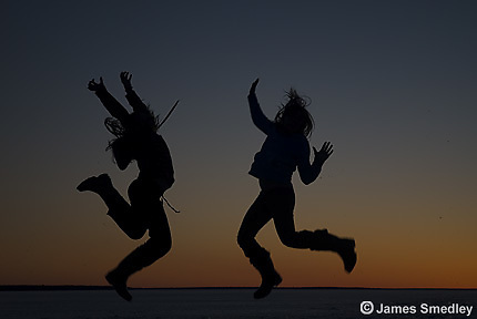 Backlit photo of girls jumping on snow covered ice in winter at sunset