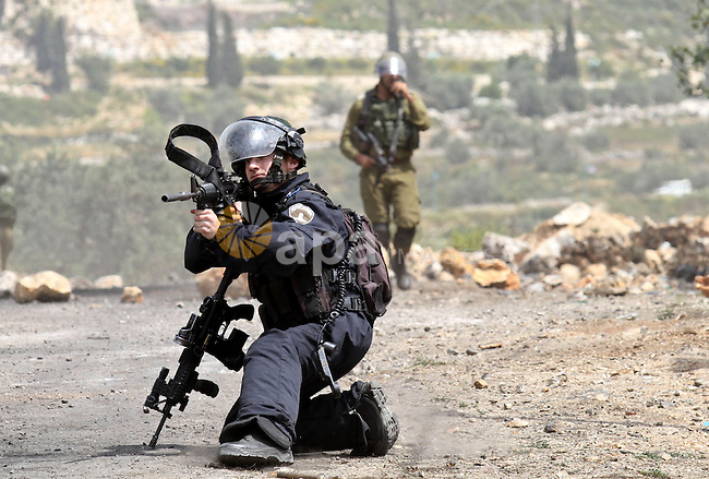 A member of Israeli security forces aims at Palestinian protesters during clashes following a protest Palestinian Prisoner's Day and against the expropriation of Palestinian land by Israel in the West Bank village of Kafr Qaddum, near the northern city of Nablus, April 17, 2015. The current number of Palestinians held in Israeli prisons is at least 6,200 and is the biggest for at least five years, according to figures from rights groups. Photo by Nedal Eshtayah