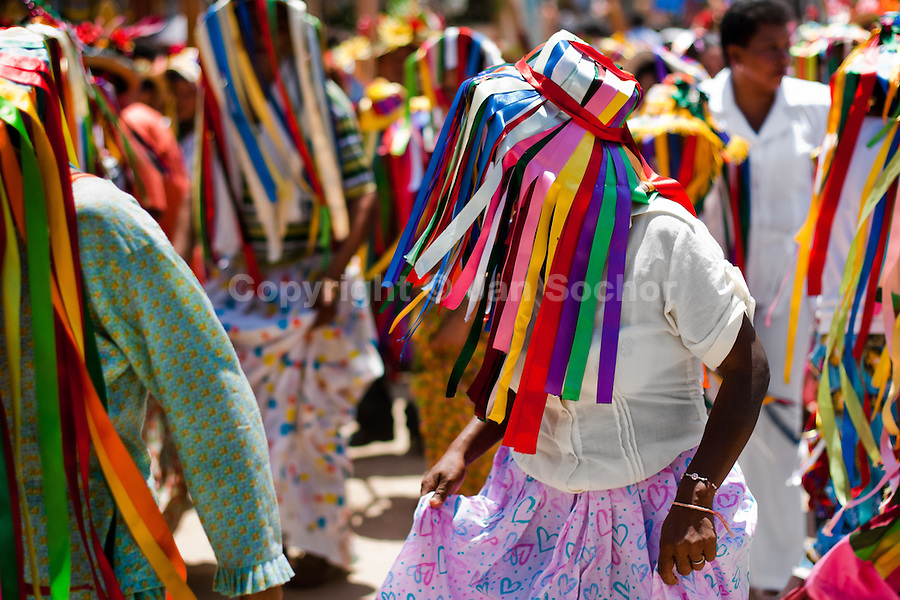 "A Negritas dancer with colorful ribbons on a hat dances in the religious procession in Atanquez, Sierra Nevada, Colombia, 3 June 2010. A colorful celebration of Corpus Christi is held in the Kankuamo Indians territory every year. ""The Dance of the Devils"" is an ancient tradition kept for centuries on the Colombia's Caribbean coast. This Christian religious event usually coincides with the summer solstice, which has always been the key point for the native cultures and for the black African slaves. Due to this confluence, the Kankuamo myths, the African animistic rites and other Pre-Columbian features have blended with the Spanish Catholic festival into a lively spectacle."