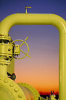 Bright yellow petroleum pipeline at sunset.