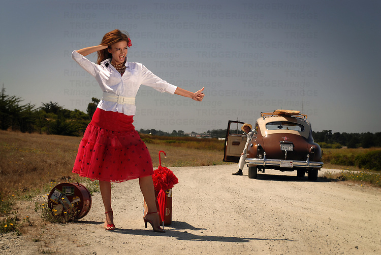 A model wearing a red skirt thumbing a lift