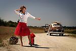 A model wearing a red skirt thumbing a lift