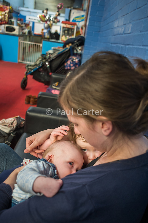A mother tandem feeds her 2.5 year old daughter and her 5 month old son at a play centre.<br /> <br /> Hampshire, England, UK<br /> 21/03/2016<br /> <br /> © Paul Carter / wdiip.co.uk