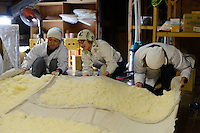 "(From left) brewery worker, Tsuji Maiko and Tsuji Soichiro handling steamed rice that is cooling on the upper level of the brewery. Tsuji Honten Sake, Katsuyama town, Okayama Prefecture, Japan, February 1, 2014. Tsuji Honten was founded in 1804 and has been at the cultural centre of the town of Katsuyama for over two centuries. 34-year-old Tsuji Soichiro is the 7th generation brewery owner. His elder sister, Tsuji Maiko, is the ""toji"" master brewer."