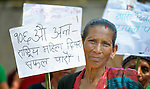 "A woman holds a sign during a march celebrating International Women's Day on March 8, 2016, in Dhawa, a village in the Gorkha District of Nepal. The sign reads, ""Let's make the 106th Women's Day a success."""