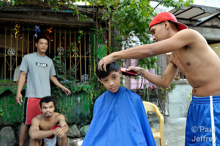 A  boy gets his hair cut in the street in the Suburban neighborhood of Rodriguez, Rizal, in the Philippines. Most of the community's families were relocated here from other area of Manila and the nearby countryside to make way for urban renewal projects or to move them out of harm's way. Yet the new community was hit hard by Typhoon Ketsana in 2009, and Christian Aid, a member of the ACT Alliance, provided emergency relief supplies. Over the years since, with help from Christian Aid and other groups, community members have organized themselves and engaged in a process of disaster risk reduction, including identifying and mapping high-risk zones and evacuation routes in their area. Christian Aid has also assisted with financial and technical support for income generating livelihood projects and community enterprises.