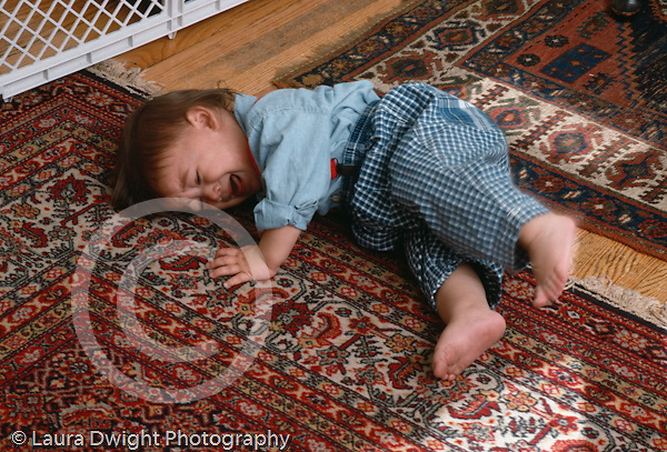 14 month old toddler boy lying on floor crying and kicking temper tantrum horizontal