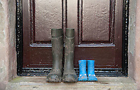 Two pairs of wellington boots, one pair a childs and one pair a male adults, outside a farmhouse door, Whitewell, Lancashire.