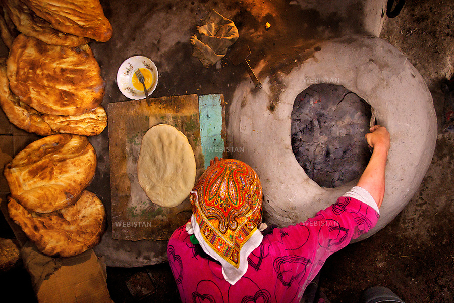 Azerbaijan, Guba district (Quba), Khinalig (Xinaliq) Village, May 7, 2012<br /> A woman cooks bread in a traditional clay oven in her home in the Khinalig Village. The northern village is referred to as &ldquo;an island in the mountain&rdquo; since is the highest and most remote village in Azerbaijan, located on a summit in the Caucasus Mountains. The village dates back at least 5,000 years and has remained virtually unchanged. The population of approximately 1,200 people belongs to the Kettidt minority. They continue to preserve their unique language (Kettish) and way of life and believe that they are the descendants of Noah.<br /> <br /> Azerba&iuml;djan, district de Gouba (Quba), village de Khinalig (Xinaliq), 7 mai 2012.<br /> Une femme fait cuire le pain dans un four traditionnel en argile dans sa maison de Khinalig. Ce village nordique est d&eacute;sign&eacute; comme &laquo; une &icirc;le dans la montagne &raquo; car il est le plus &eacute;lev&eacute; et le plus recul&eacute; du pays, localis&eacute; au sommet des montagnes du Caucase. Vieux de plus de 5 000 ans, il n&rsquo;a pratiquement pas chang&eacute; au fil du temps. Ses 1200 habitants appartiennent &agrave; la minorit&eacute; Kettidt et ont pr&eacute;serv&eacute; leur langue unique (kettish), leur mode de vie. Ils pensent &ecirc;tre les descendants de No&eacute;.<br /> <br /> Distribution HEMIS