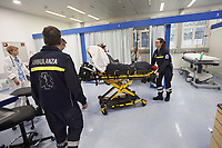 Switzerland. Canton Ticino. Lugano. Clinica Luganese Moncucco. Emergency room. A senior man is brought by ambulance to the clinic for medical examinations. The elderly man is suffering from severe respiratory problems. The paramedics team is delivering the patient to the woman doctor with the white blouse. The emergency doctor Daniele Speciale (C) is closely working with two paramedics. The paramedics work for the Croce Verde Lugano and wear blue uniforms. The woman (R) is a professional certified nurse, the man (L) is a volunteer specifically trained in emergency rescue. The doctor is permanently controlling health's state of the aged patient. The senior citizen has a mask on his face and receives oxygen from a medical ventilator. A medical ventilator (or simply ventilator in context) is a mechanical ventilator, a machine designed to move breathable air into and out of the lungs, to provide breathing for a patient who is physically unable to breathe, or breathing insufficiently. A monitor controls the patient's vital functions, such as electrocardiogram, blood pressure's measurement, respiratory rate and pulse oximetry (oxygen saturation). On the man's arm, an intravenous infusion with saline solution is fixed. The Croce Verde Lugano is a private organization which ensure health safety by addressing different emergencies services and rescue services. Volunteering is generally considered an altruistic activity where an individual provides services for no financial or social gain to benefit another person, group or organization. Volunteering is also renowned for skill development and is often intended to promote goodness or to improve human quality of life. 14.01.2018 © 2018 Didier Ruef