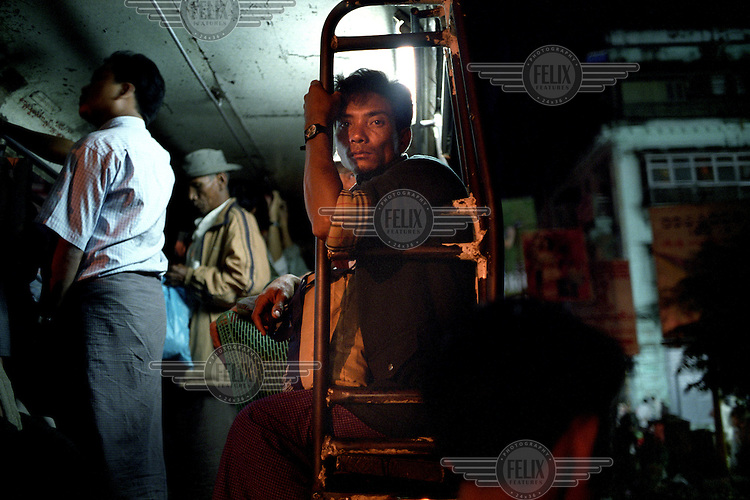 A man sits on the edge of a commuter bus, waiting to be transported to the outskirts of the city. Other commuters sit and stand inside the bus. ..