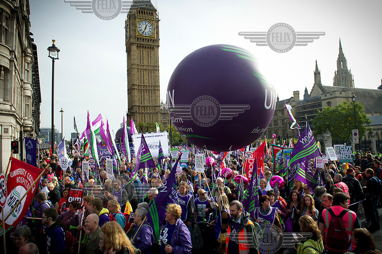 UNISON (Britain's biggest union) demonstrators march past the Houses of Parliament in Westminister, London during a protest called by the TUC (Trades Union Congress). The demonstration was made under the rallying cry of 'Marching for a Future that Works', a protest against the austerity policies of Britain's coalition government.