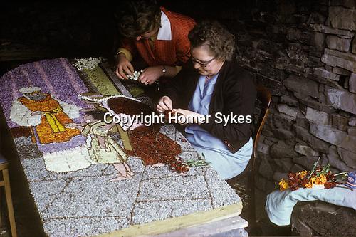 Tissington Well Dressing, local women make the wild flower floral display boards. Derbyshire UK